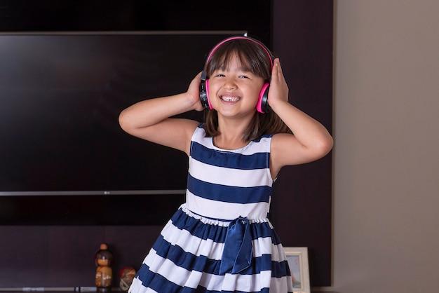 Szczęśliwa śliczna mała dziewczynka słuchanie muzyki
