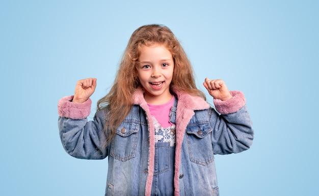 Szczęśliwa śliczna mała dziewczynka w modnej ciepłej dżinsowej kurtce, trzymając pięści w górze, mając szczęście i świętując sukces