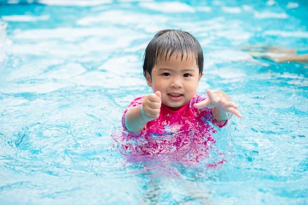 Szczęśliwa śliczna mała dziewczynka w pływackim basenie. lato na zewnątrz.