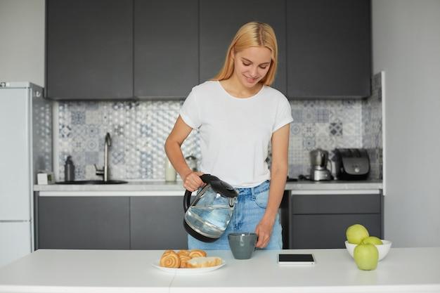 Szczęśliwa śliczna młoda blondynka w dobrym nastroju stoi przy stole, uśmiecha się, je śniadanie i parzy herbatę w dużej szarej filiżance