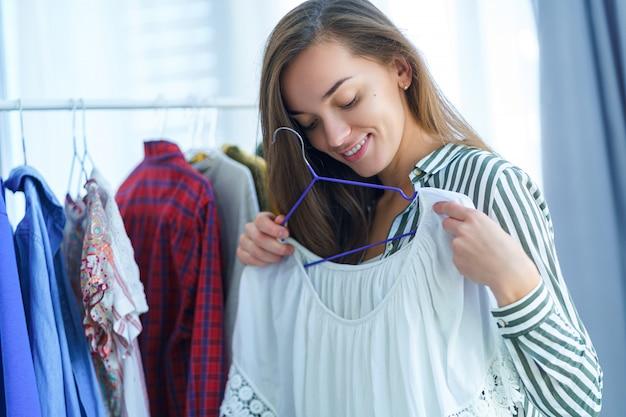 Szczęśliwa śliczna młoda brunetki kobieta stoi blisko szafa garderoby stojaka pełnego stylowych modnych ubrań na wieszakach i próbuje odzież podczas wybierania w co się ubrać