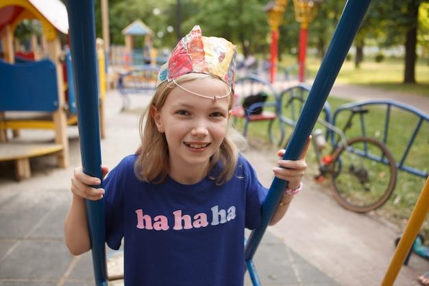 Szczęśliwa śliczna młoda dziewczyna śmiejąca się, siedząca na huśtawce na placu zabaw