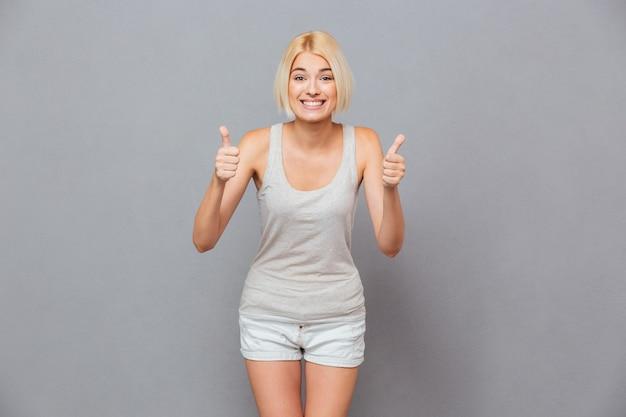 Szczęśliwa śliczna młoda kobieta pokazując kciuk do góry obiema rękami nad szarą ścianą