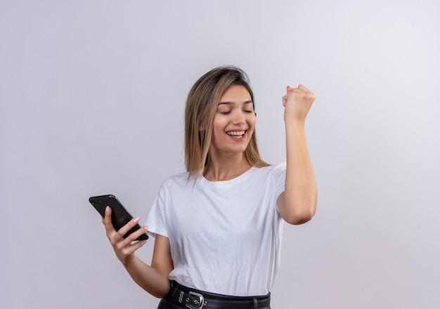 Szczęśliwa śliczna młoda kobieta w białej koszulce podnosząca zaciśniętą pięść, trzymając telefon komórkowy na białej ścianie