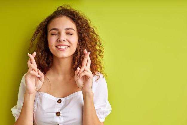 Szczęśliwa śliczna młoda kobieta z kręconymi włosami trzyma kciuki, koncepcja szczęścia