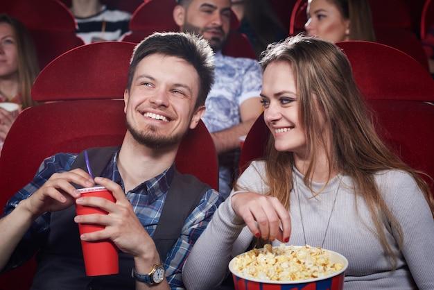 Szczęśliwa śliczna para je popcorn i śmieje się z śmiesznej komedii w kinie. atrakcyjna dziewczyna i przystojny mający romantyczną randkę i cieszący się ciekawym filmem. pojęcie rozrywki.