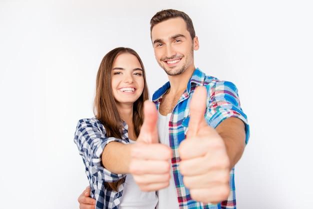 Szczęśliwa śliczna para zakochanych obejmując siebie pokazując kciuki do góry