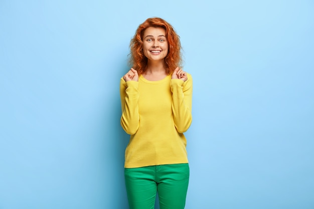 Szczęśliwa śliczna rudowłosa kobieta zaciska pięści, czuje się świetnie po wygranej konkurencji, ubrana niedbale