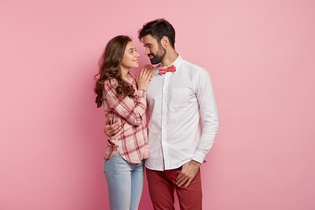 Szczęśliwa słodka para zakochanych przytula się i patrzy na siebie z delikatnym uśmiechem, ubrana w stylowe eleganckie ubrania