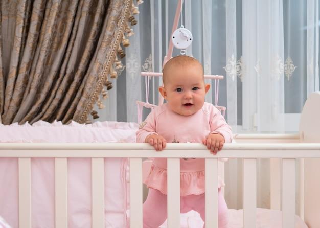 Szczęśliwa, śmiejąca się dziewczynka stojąca w łóżeczku w różowej scenie sypialni.