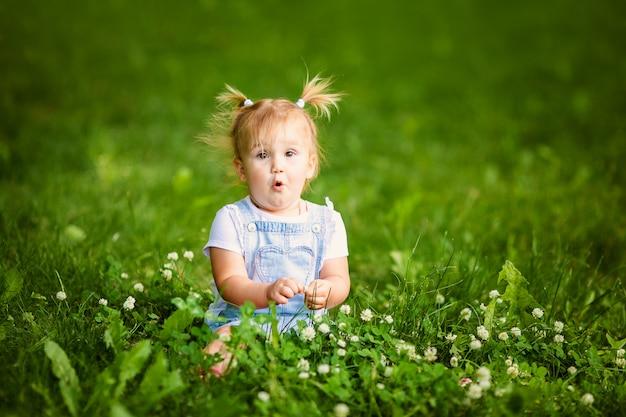 Szczęśliwa śmieszna dziewczynka z dwa małymi warkoczami siedzi na zielonej trawie