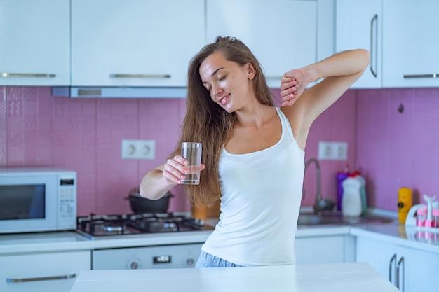 Szczęśliwa śpiąca kobieta rozciąga się i pije szklankę czystej, oczyszczonej porannej wody wczesnym rankiem po przebudzeniu w kuchni w domu. początek i początek nowego dobrego dnia