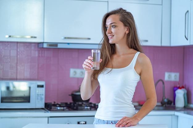 Szczęśliwa śpiąca radosna kobieta pije szklankę czystej, oczyszczonej porannej wody wczesnym rankiem po przebudzeniu w kuchni w domu. początek i początek nowego dobrego dnia