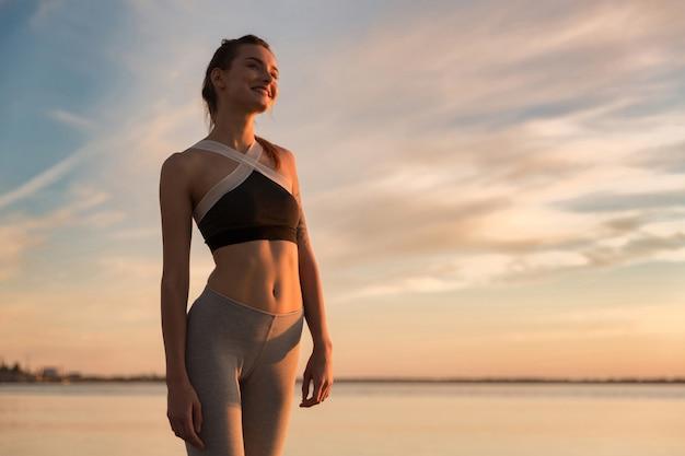 Szczęśliwa sport kobieta patrzeje na boku przy plażą.