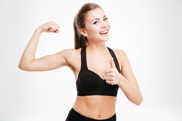 Szczęśliwa sportowa kobieta pokazująca znak ok i biceps na białym tle
