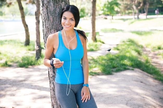 Szczęśliwa sportowa kobieta stojąca z smartphone na zewnątrz