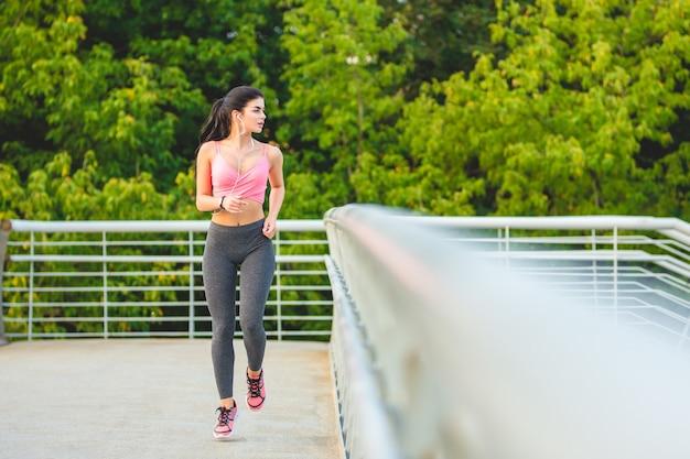 Szczęśliwa sportsmenka biegająca po moście