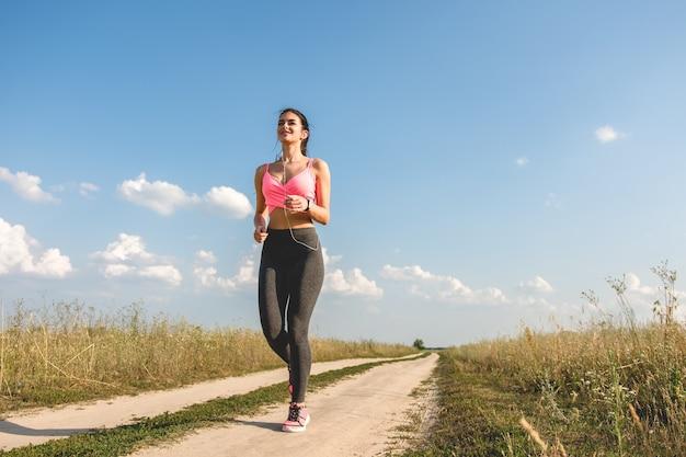 Szczęśliwa sportsmenka biegająca po ścieżce w terenie