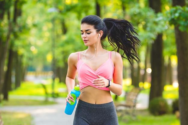 Szczęśliwa sportsmenka biegająca w parku