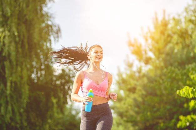 Szczęśliwa sportsmenka biegająca z butelką na słonecznym tle