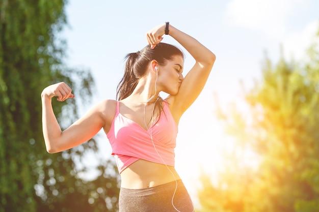 Szczęśliwa sportsmenka całująca jej bicepsy na słonecznym tle
