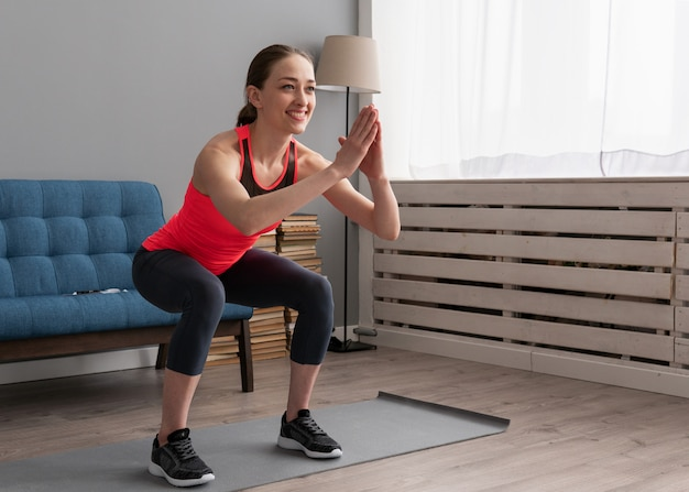 Szczęśliwa sprawności fizycznej kobieta robi kucającemu ćwiczeniu w domu