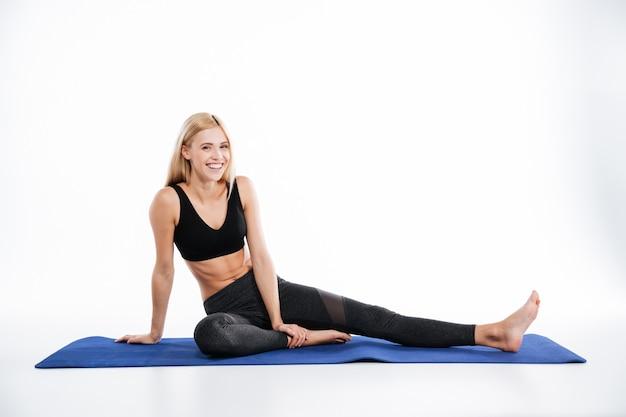Szczęśliwa sprawności fizycznej kobiety obsiadanie i pozować
