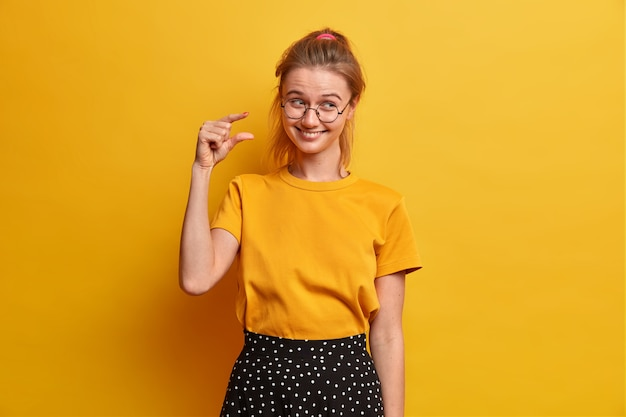 Szczęśliwa sprytna uczennica demonstruje małą ilość czegoś, mierzy bardzo małą rzecz, wyjaśnia, jak bardzo była zainteresowana podczas lekcji, nosi okulary optyczne