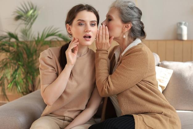 Szczęśliwa średnia matka szepcząc sekret do swojej uśmiechniętej córki w domu, plotkując, dzieląc się sekretem. piękna kobieta słysząca dobre wieści od dojrzałej mamy, zaufane relacje.