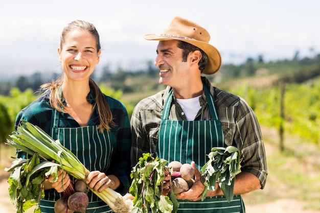 Szczęśliwa średniorolna para trzyma obfitolistnych warzywa