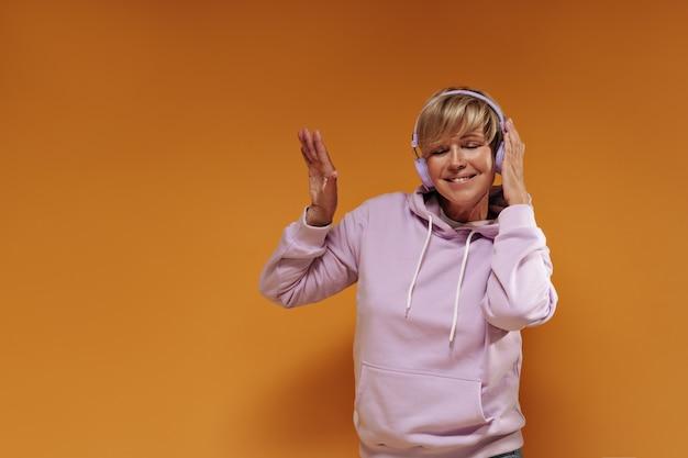 Szczęśliwa stara kobieta z blond fryzurą i fajnymi słuchawkami w różowej bluzie z kapturem, uśmiechając się i słuchając muzyki na pomarańczowym tle.