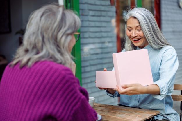 Szczęśliwa starsza azjatycka dama otwiera prezent z najlepszym przyjacielem świętującym wakacje w kawiarni