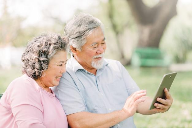 Szczęśliwa starsza azjatycka para używa cyfrową pastylkę