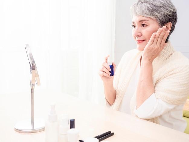 Szczęśliwa starsza azjatykcia kobieta stosując balsam do jej twarzy.