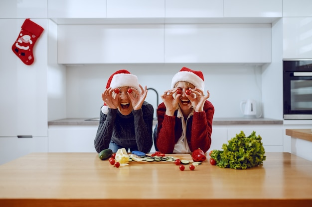 Szczęśliwa starsza kobieta i jej córka, opierając się na blacie kuchennym i trzymając na oczach plasterki pomidora cherry. obaj mają na głowach czapki mikołaja. na blacie kuchennym są warzywa.
