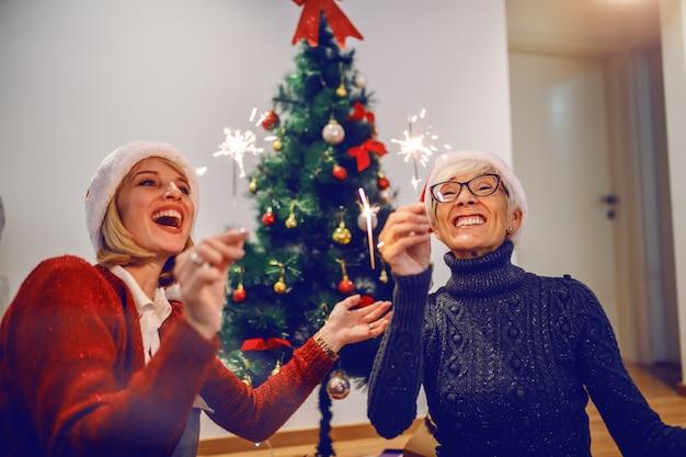 Szczęśliwa starsza kobieta i jej córka świętuje nowy rok. obie mają na głowach czapki mikołaja i trzymają zimne ognie. pojęcie wartości rodzinnych.