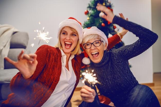 Szczęśliwa starsza kobieta i jej córka świętuje nowy rok. obie mają na głowach czapki mikołaja i trzymają zimne ognie. w tle jest choinka. pojęcie wartości rodzinnych.