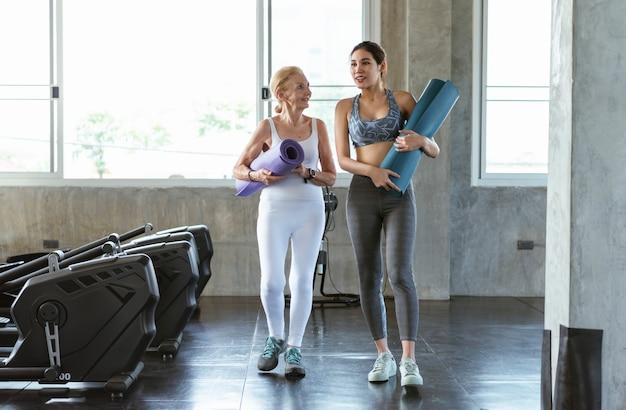 Szczęśliwa starsza kobieta i młoda nastolatka na siłowni jogi. ćwiczyć zdrowy styl życia.