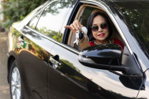 Szczęśliwa starsza kobieta jedzie jej nowego samochodu klucz i pokazuje.