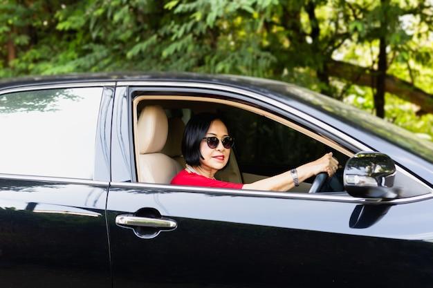 Szczęśliwa starsza kobieta jedzie samochód w okularach przeciwsłonecznych.