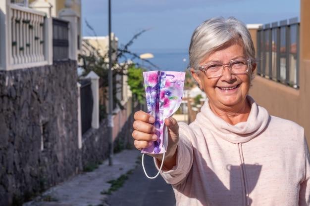 Szczęśliwa starsza kobieta już zaszczepiona przeciwko zakażeniu koronawirusem uśmiechnięta na zewnątrz, biorąc do ręki maskę ochronną. nieostre ludzie