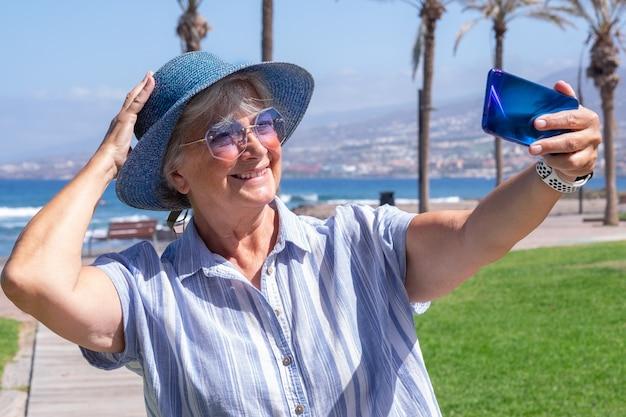 Szczęśliwa starsza kobieta na morzu korzystających z wakacji. przystojna influencerka w streamingu wideo