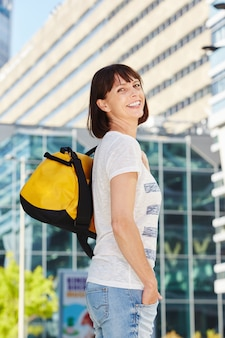 Szczęśliwa starsza kobieta niesie duffel torbę w mieście