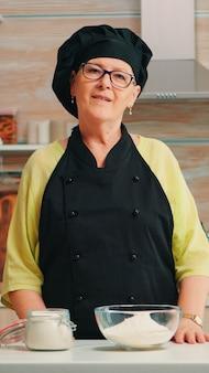 Szczęśliwa starsza kobieta nosi bonete patrząc na camrea w jadalni w domu. emerytowany stary piekarz w mundurze kuchennym przygotowuje składniki piekarnicze na stole gotowy do gotowania domowego chleba, ciast i makaronów.