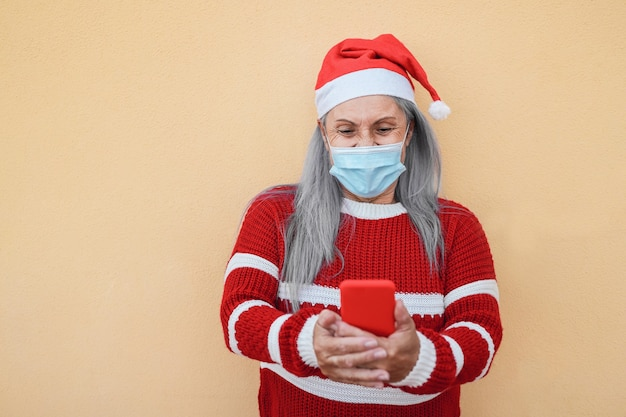 Szczęśliwa starsza kobieta nosi kapelusz świętego mikołaja i maskę podczas korzystania z telefonu komórkowego