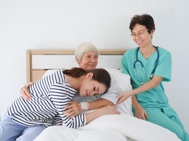 Szczęśliwa starsza kobieta opowiada z starszą pielęgniarką i jej córką w sala szpitalnej.