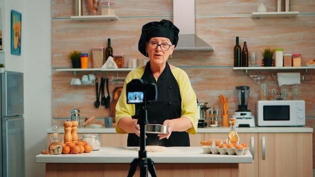 Szczęśliwa starsza kobieta piekarz filmowanie vlog gotowania w domowej kuchni. emerytowany bloger, wpływowy szef kuchni, korzystający z komunikacji internetowej, kręcenia blogów w mediach społecznościowych za pomocą sprzętu cyfrowego