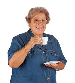 Szczęśliwa starsza kobieta pije kawę