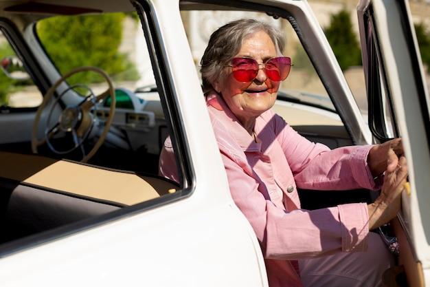 Szczęśliwa starsza kobieta podróżująca samotnie samochodem