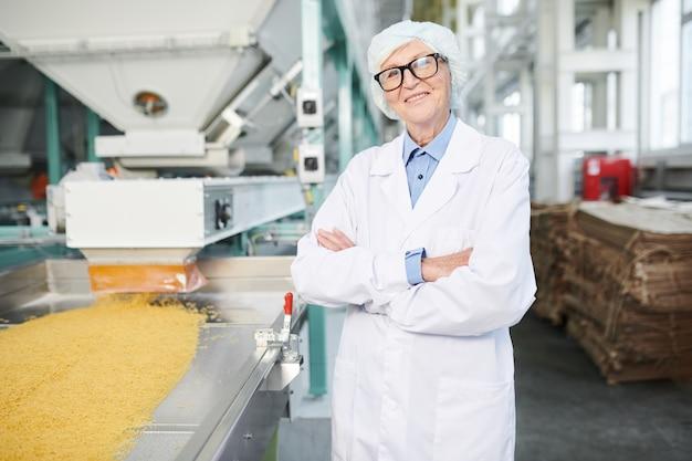 Szczęśliwa starsza kobieta pozuje przy fabryką